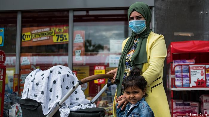 A woman in a head scarf and medical face mask pushes a pushchair and holds her young daughter's hand