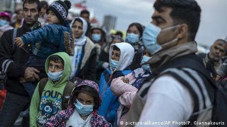 Refugees and migrants wearing masks to prevent the spread off the coronavirus, wait to get on a bus after their arrival at the port of Piraeus (picture-alliance/AP Photo/P. Giannakouris)