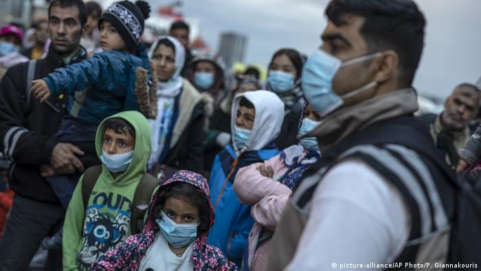 Refugees and migrants wearing masks to prevent the spread off the coronavirus, wait to get on a bus after their arrival at the port of Piraeus