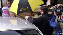 The very top of Claudia Schiffer's head-dress is just visible below the umbrella, as security guards try to cover the German model/ actress , as she makes her way to her wedding car, Saturday May 25, 2002. She left the Swan Hotel, Lavenham, Suffolk, to a chorus of jeering from local spectators who had turned out to see her wedding to film producer Matthew Vaughn. (AP PHOTO/ MARTYN HAYHOW)