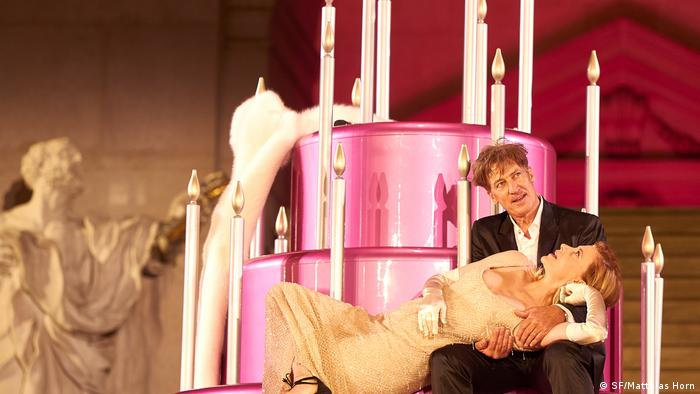 Actors Tobias Moretti (Jedermann), Caroline Peters (Buhlschaft) on stage performing in front of a giant pink cake with candles