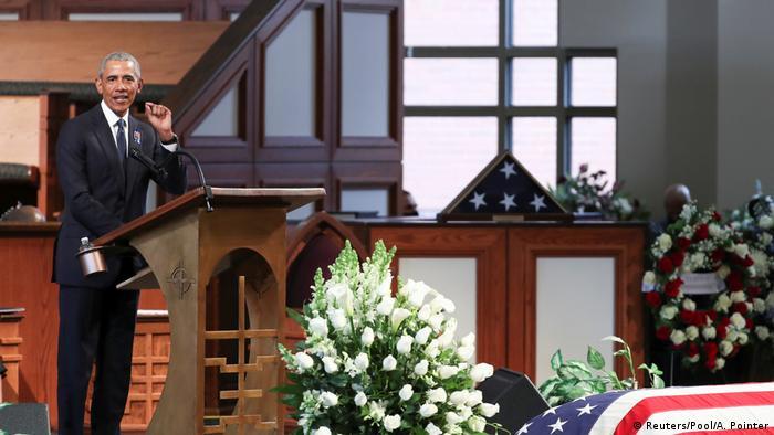 Obama discursa em púpito, Pode-se ver parte do caixão de Lewis coberto com a bandeira americana.