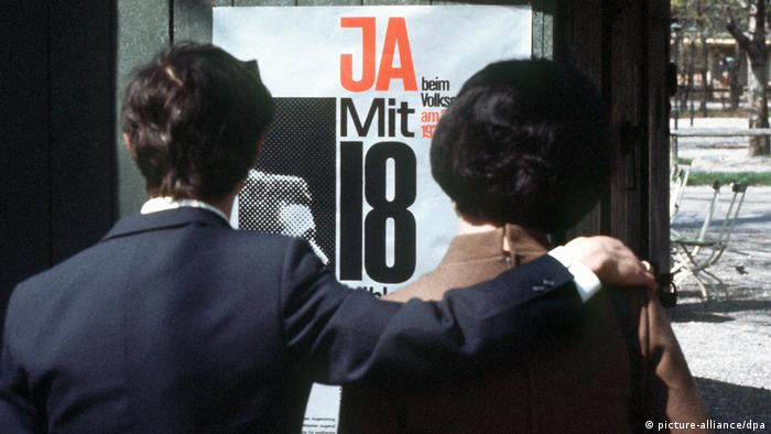 A young couple in an undated photo probably hailing from the late 1960s or 1970 look at a poster calling for the voting age in Germany to be reduced to 18. (picture-alliance/dpa)
