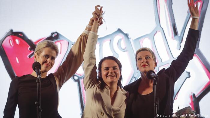 Svetlana Tikhanovskaya at a rally holds up her hands