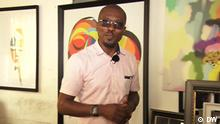 Eco Africa presenter Nneota Egbe in front of some colorful artworks