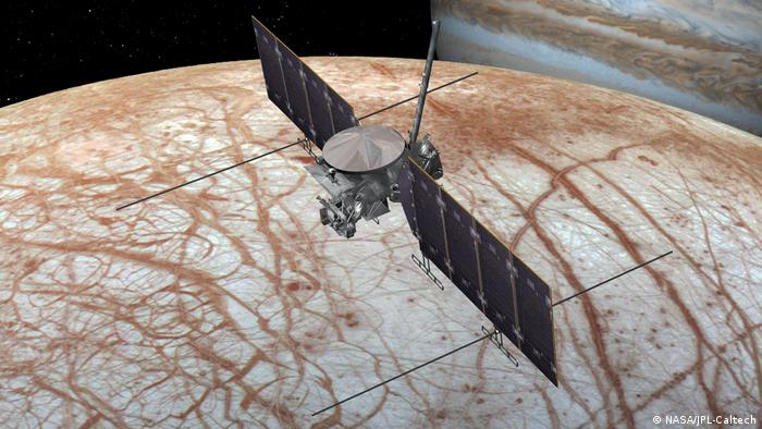 An artist's rendering shows NASA's Europa Clipper spacecraft over Jupiter's moon, Europa. The moon shows red streaks.