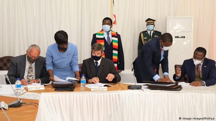 President Emmerson Mnangagwa (left, rear) at the signing ceremony of the compensation agreement for white farmers