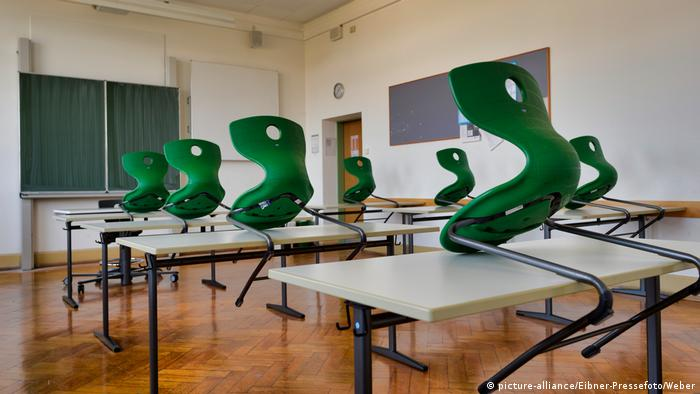 classroom with tables and green chairs set on the tables