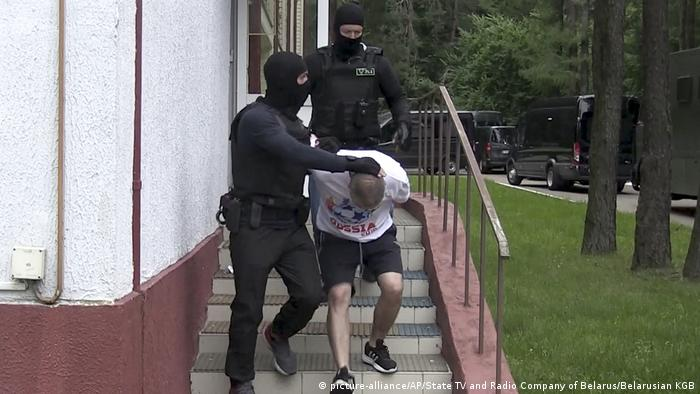 A Belarussian security officer dressed entirely in black leads away an alleged Russian mercenary, who is bent over