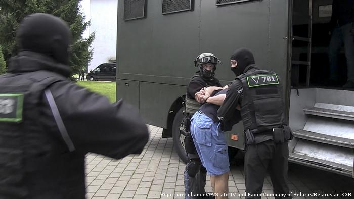In this photo taken from video released by Belarusian KGB, State TV and Radio Company of Belarus on Wednesday, July 29, 2020, Belarusian KGB officers detain a Russian man in a sanitarium outside in Minsk, Belarus.