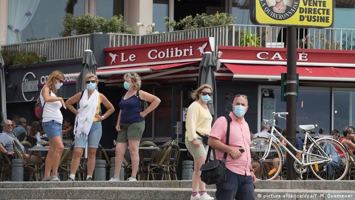 People wear face masks outside in the French city of Quiberon, where a local outbreak of coronavirus was discovered in July 2020