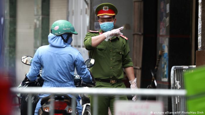 Em frente a bloqueio, policial em Hanói indica caminho de desvio para motoqueiro