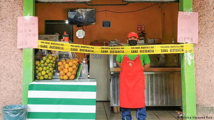 Un vendedor de jugos de fruta, detrás de una banda con la inscripción: Sana distancia, en Ciudad de México.