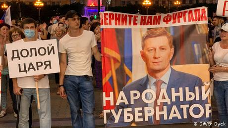 Protesters with banners, one saying 'Down with the czar,' one calling for Furgal's release