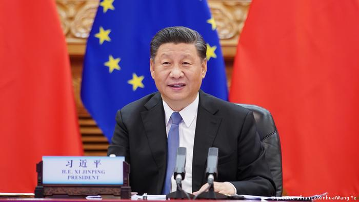China President Xi Jinping sits in front of Chinese and EU flags