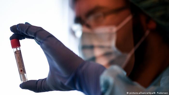 Homem de proteção sanitária segura teste de covid-19 na mão