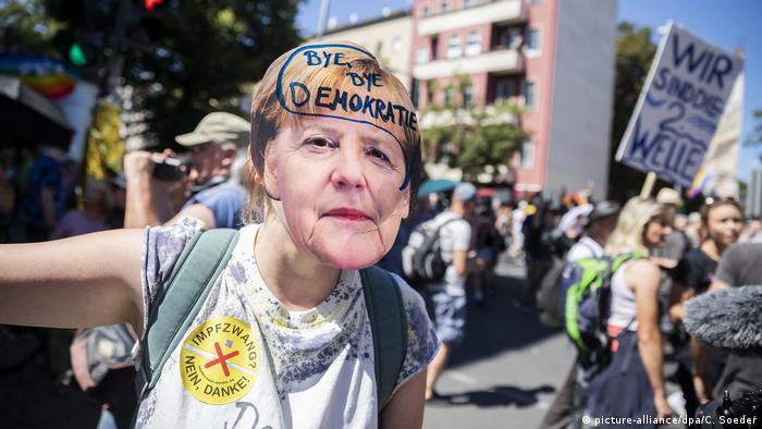 Protestatarii se opun măsurilor de îngrădire a răspândirii SARS-CoV-2 şi o învinuiesc pe cancelara Merkel (picture-alliance/dpa/C. Soeder)