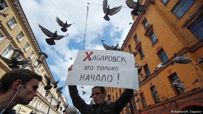 Один из участников акции в поддержку хабаровчан в Санкт-Петербурге держит в руках плакат с надписью Хабаровск - это только начало!, а над его гловой кружат голуби.