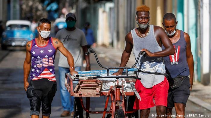 Homens de máscara sanitária puxam carreta
