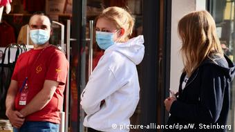 Homem e duas mulheres em fila usando máscara naso-bucal