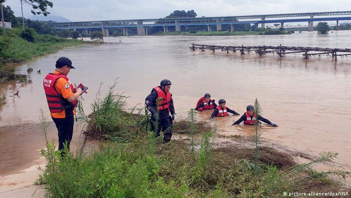 Feuerwehrleute waten durch Wasser, das ihnen bis zur Brust reicht (Foto: picture-alliance/dpa/YNA)