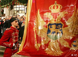 A traditionally dressed soldier watches the national flag being lifted at the Montenegrin parliament