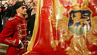 A traditionally dressed soldier watches national flag being lifted after Montenegrin parliament deputies voted to proclaim independence in Podgorica, Saturday, June 3 2006. Montenegro's parliament declared independence for the tiny Balkan republic, forming a new European state and formally dissolving what was left of Yugoslavia. The assembly verified the results of a May 21 referendum when the Montenegrins supported a split from the Serbia-Montenegro union by a slim margin and formally proclaim a declaration on independence. (AP Photo/Srdjan Ilic)