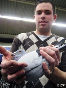A boy holds the pigeon his friend just bought at a pigeon auction in Dortmund.