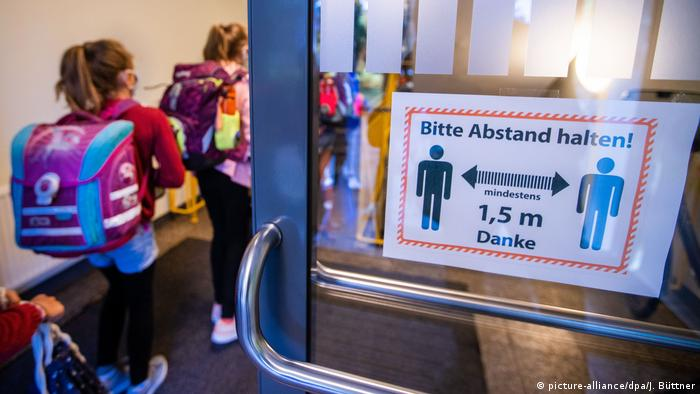 Children entering a school with a sign admonishing them to keep 1.5 meters distance