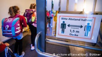 Дети в школьном коридоре, на двери висит плакат с призывом сохранять дистанцию в 1,5 метра