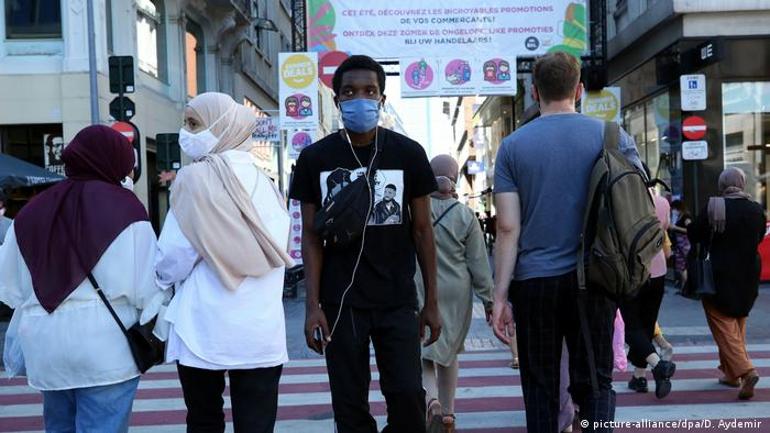 People wearing medical face masks walk down a street in Brussels, Belgium