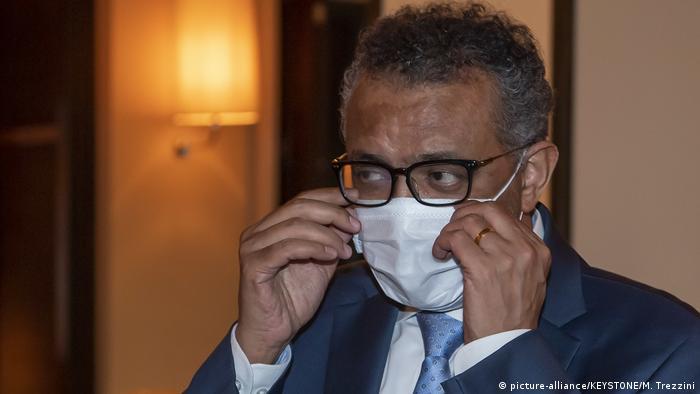 WHO chief Tedros Adhanom Ghebreyesus dons a mask (picture-alliance/KEYSTONE/M. Trezzini)