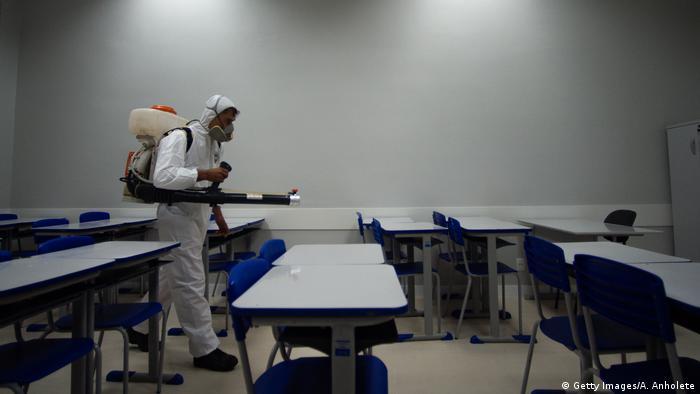 Pessoa com roupas de proteção desinfeta sala de aula vazia