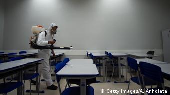 Человек в костюме химзащиты дезинфицирует школьный класс в Бразилии