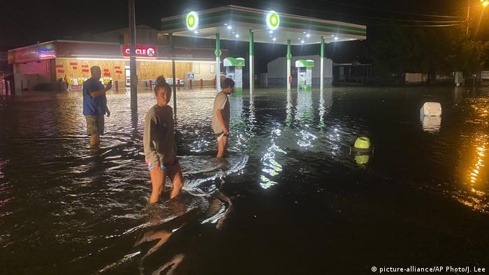 People walk through knee-high flood waters at petrol station (picture-alliance/AP Photo/J. Lee)