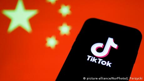 TikTok logo is seen displayed on a phone screen with Chinese flag in the background
