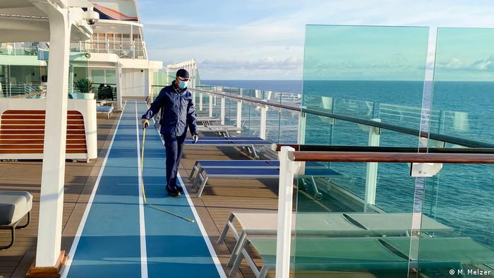 A crew member on a cruise ship is measuring out the distances between chairs on the sun-deck.