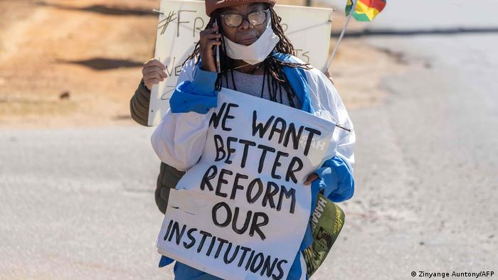 Zimbabwean novelist Tsitsi Dangarembga holds a placard during an anti-corruption protest in July 31 2020 in Harare