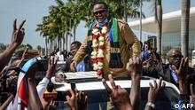 TOPSHOT - Tundu Lissu (C), Tanzania's former MP with the Chadema main opposition party, who was shot 16 times in a 2017 attack, reacts to supporters as he returns after three years in exile to challenge President John Magufuli in elections later this year, at Julius Nyerere International Airport in Dar es Salaam, Tanzania, on July 27, 2020. - Tanzania will hold a general election on October 28, 2020. (Photo by STR / AFP)
