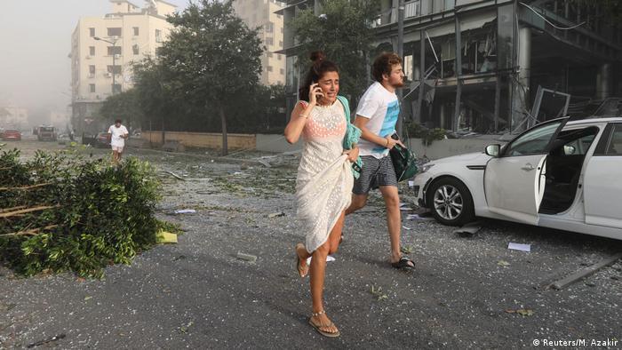 Hombre y mujer huyen del área devastada por las explosiones