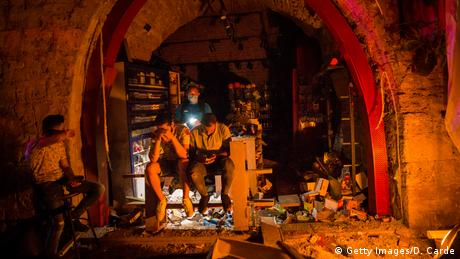 A group of men sit near the entrance of a shop damaged after a large explosion on August 4, 2020 in Beirut, Lebanon.