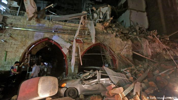 People stand by building and car in ruins in the evening| Gewaltige Explosion in Beirut (Getty Images/AFP/STR)