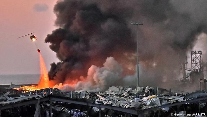 Ein Löschhubschrauber lässt ein Brandbekämpfungsmittel über einem Feuer ab (Getty Images/AFP/STR)