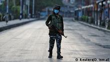 An Indian police officer patrols on a street in Srinagar during a lockdown on the first anniversary of the revocation of Kashmir's autonomy