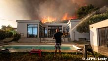 A man uses a garden hose to drench his house before being evacuated as a wild fire burns in the background, in La Couronne, near Marseille