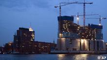 Die Baustelle der Elbphilharmonie steht am Dienstag, 30. Maerz 2010 im Abendlicht am Ufer der Elbe in Hamburg. Leicht und weiss und spitz wie eine nach oben gefaltete Serviette soll die Glaskonstruktion einmal auf dem schweren Backsteinbau liegen. Bisher aber sieht man wenig davon im Hamburger Hafen. Baukraene drehen sich, Planen verdecken den Rohbau der monumentalen Elbphilharmonie, die das neue Wahrzeichen der Stadt werden soll und ein Prestige-Projekt fuer Buergermeister Ole von Beust. Doch keiner glaubt mehr an eine rechtzeitige Fertigstellung wie einst geplant im Mai 2012. (apn Photo/Axel Heimken) ** zu unserem KORR. APD9958 ** --- The construction site of the philharmonic hall 'Elbphilharmonie' is pictured in the evening light in Hamburg, northern Germany, on Tuesday, March 30, 2010. (apn Photo/Axel Heimken)