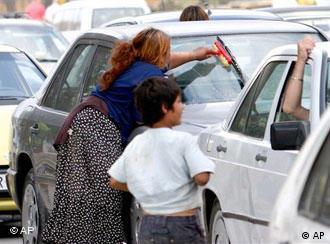 Djevojka pere prozor na automobilu, pored nje stoji dječak