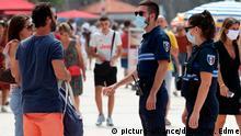03.08.2020, Frankreich, Biarritz: Polizeibeamte weisen Passanten auf das Tragen einer Mund-Nasen-Bedeckung hin. Im Kampf gegen Corona gilt in weiteren französischen Gemeinden jetzt eine Maskenpflicht im Freien. Foto: Bob Edme/AP/dpa +++ dpa-Bildfunk +++