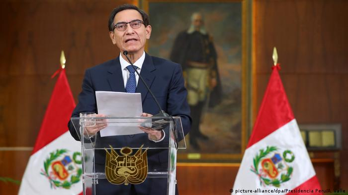 Martín Vizcarra, presidente do Peru, fala em púlpito entre duas bandeiras peruanas
