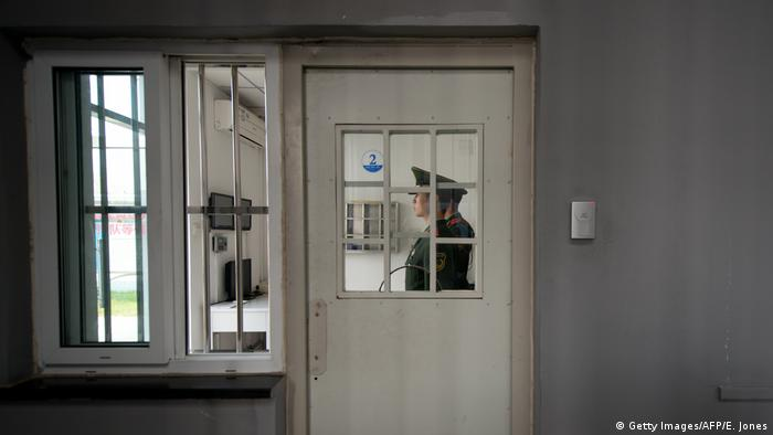 A paramilitary guard stands at a security door inside the No.1 Detention Center during a government guided tour in Beijing on October 25, 2012. (Getty Images/AFP/E. Jones)